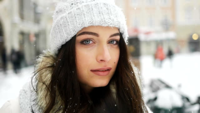 street emotional portrait of young beautiful woman in city model looking at camera. lady wearing stylish classic winter knitted clothes. christmas concept. snowfall - abiti pesanti video stock e b–roll