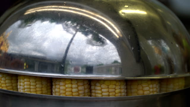 Street fast food. Cooking corn in boiled water. Sweet corn sold at city market harvest festival. City street reflected in the lid of the pan. Concept healthy lifestyle video