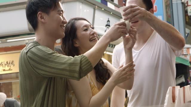MONTAGE - Street Food Friends Sidewalk Drinking Slow motion Japan. video