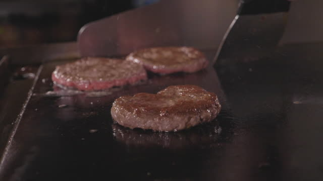 Street food restaurant, close-up grilling tree burgers cutlet on frying surface video