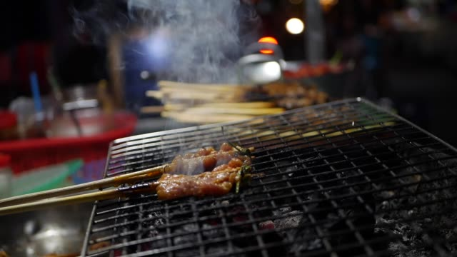 Street food vendor prepares and sells grill pork on sticks, bbq fried pork meat at night market. Closeup.4k Street food vendor prepares and sells grill pork on sticks, bbq fried pork meat at night market. Closeup skewer stock videos & royalty-free footage