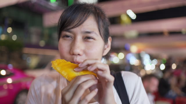 Street Food - Young woman eating mango in Yaowarat Road, Bangkok, Thailand Street Food - Young woman eating mango in Yaowarat Road, Bangkok, Thailand mango stock videos & royalty-free footage