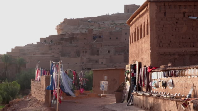 street market stall in a small traditional moroccan village without people, scarves and souvenirs being sold on both sides in ait benhaddou. - souk video stock e b–roll