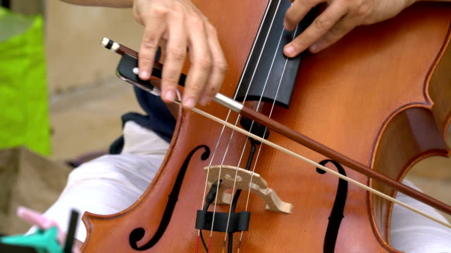 Street musican plays beautifully on cello on a summer day.