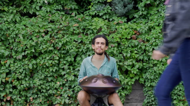 MONTAGE: Street musician playing handpan (sound/audio available)