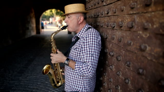 Street musician with a hat on his head play saxophone