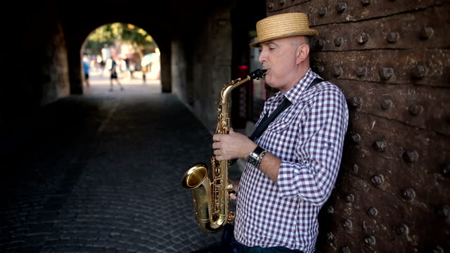 Street musician with a hat on his head play saxophone video