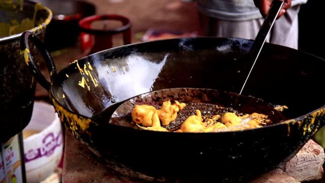 Street seller frying pakode Street seller frying gram flour pakode on his stall in the market. haryana stock videos & royalty-free footage