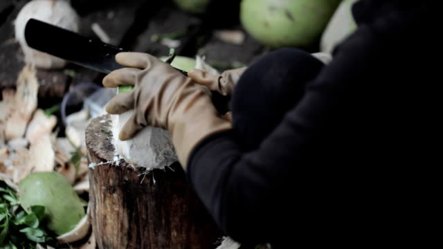 Street seller opening coconut with a big knife. video