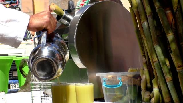 strada venditore versare succo di bambù - canna da zucchero video stock e b–roll