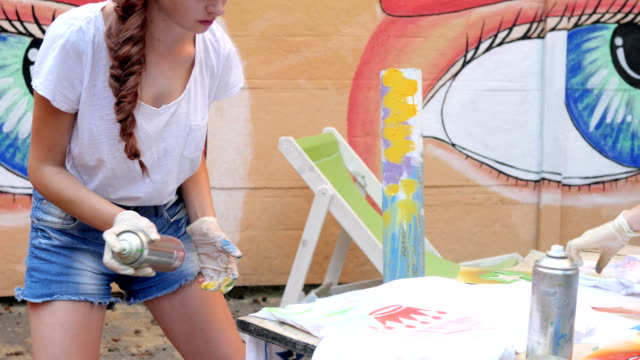 street style, girl with spray paint in hand, adolescent with aerosol paint at background of graffiti in slow motion