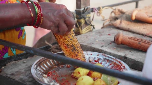 vidéos et rushes de vendeur de rue est frottant un épi de maïs sucré rôti avec du citron et des épices. - maïs culture