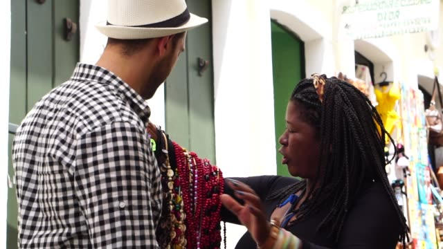 street vendor welcoming and selling his products to the tourist in salvador, bahia, brazil - prodotto d'artigianato video stock e b–roll