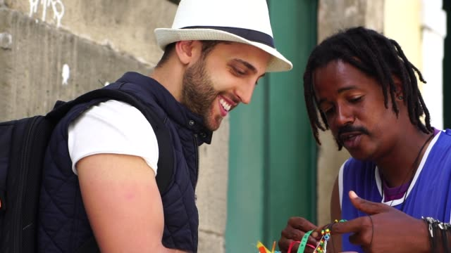 Street Vendor Welcoming Tourist Giving Some Brazilian Ribbons (Fita do Bonfim) on in Salvador, Bahia, Brazil video