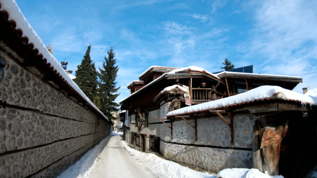 street view, traditional houses and high snow in bulgarian ski resort - negozio sci video stock e b–roll