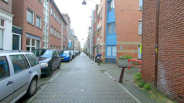 Street with parked cars in Amsterdam. Residential area of Amsterdam.  Cars are parked along the street. dutch architecture stock videos & royalty-free footage