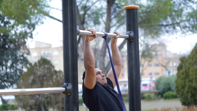 Street workout training. gym man doing pull-ups with resistance band on outdoor gym in the park. video