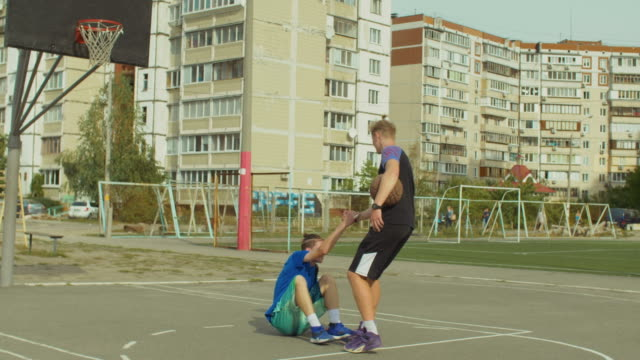 Streetball player helping fallen opponent to stand up