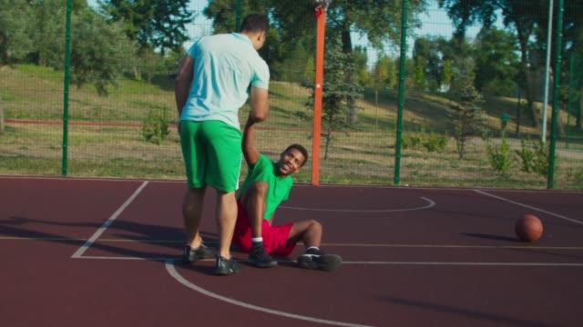 vídeos de stock, filmes e b-roll de jogador de streetball ajudando adversário a se levantar - consciência negra