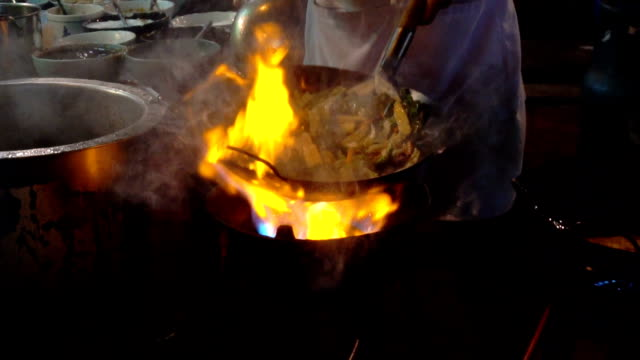street-side wok fire in chinatown bangkok. cook fired up hot oil with vegetables outside on the road at night in downtown yaowarat road food street in thailand. - ночной рынок стоковые видео и кадры b-roll