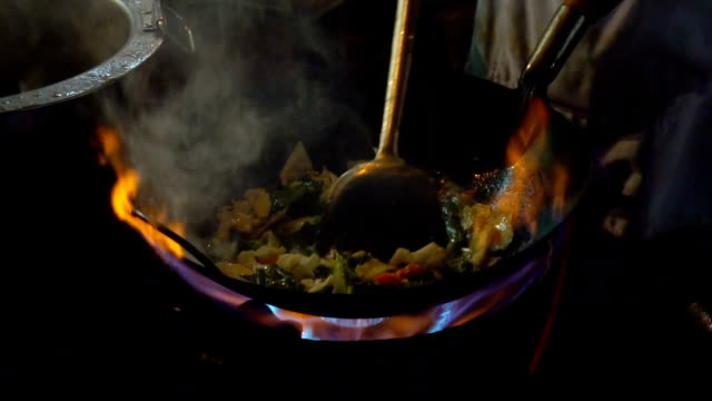 street-side wok fire in chinatown bangkok slow motion. cook fired up hot oil with vegetables outside on the road at night in downtown yaowarat road food street in thailand. - ночной рынок стоковые видео и кадры b-roll