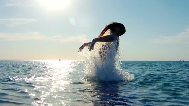 vídeos de stock, filmes e b-roll de homem da força que banha-se no mar que joga o cabelo longo cercado espirrando no por do sol - domínio