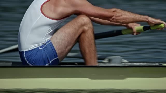 vídeos de stock, filmes e b-roll de força de ts de uma atleta de remo masculino deslizando sobre um lago no remo - remo esporte aquático