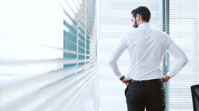 stresfull businessman standing by the window. - communication problems stock videos & royalty-free footage