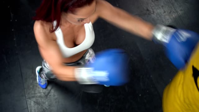 stress relief - overhead top shoot of a woman punching the bag in gym - sacco per il pugilato video stock e b–roll