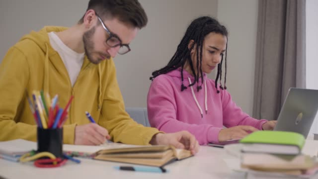 Stressed African American girl closing laptop and crossing hands as her male Caucasian groupmate in eyeglasses rolling eyes and writing in workbook. Education, difficulties, studying.