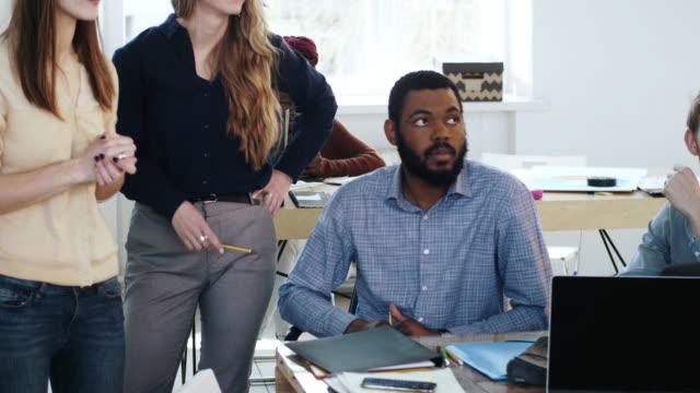 stressad och upprörd afrikansk manlig anställd sitter vid moderna kontor bord upptagen med pappersarbete nära två kvinnliga kollegor. - etnicitet bildbanksvideor och videomaterial från bakom kulisserna
