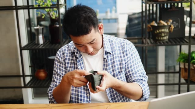 Stressed Asian man showing empty black wallet, slow motion.