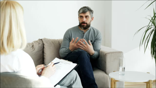 Stressed bearded man talking about his problems to psychologist in her office indoors video