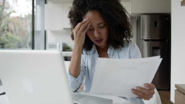 vídeos de stock e filmes b-roll de stressed black woman working from home looking at a document very upset - conta acessório financeiro