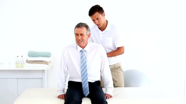 Empresário estressado se sua volta marcada por um fisioterapeuta - vídeo