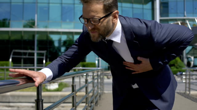 vídeos de stock e filmes b-roll de stressed businessman having heart attack outdoors, strong chest pain, first aid - ataque cardíaco