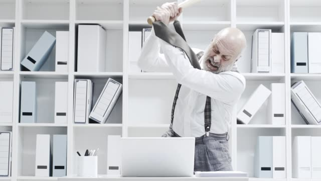 Stressed businessman smashing his laptop with a bat