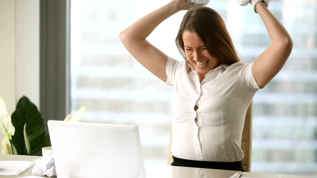 Stressed female employee throwing crumpled paper, nervous breakdown at work video