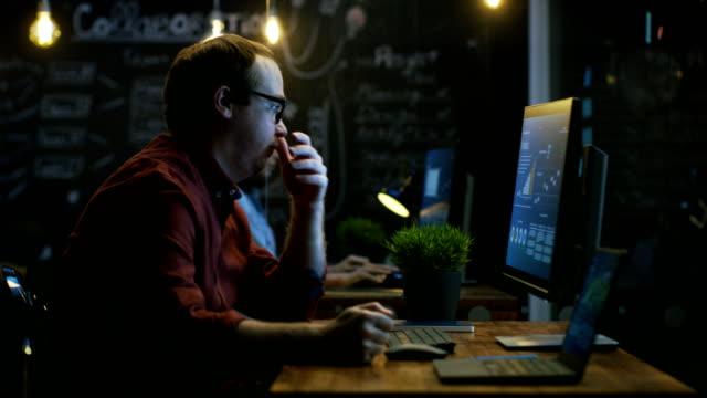 資本家ヒット欲求不満で彼はこぶしでテーブルを強調し、手で顔を覆います。画面上の表示の統計情報を個人のコンピューターに取り組んでいます。 - 悩む点の映像素材/bロール