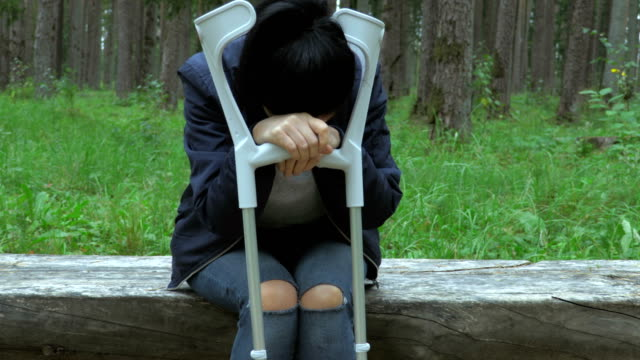 Stressed Injured Female on Crutches on bench.Anxiety concept Stressed Injured Female on Crutches on bench.Anxiety concept crutch stock videos & royalty-free footage