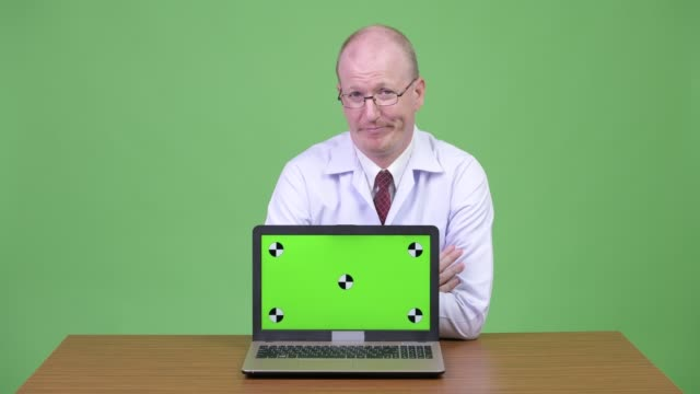 Stressed mature bald man doctor talking and showing laptop against wooden table