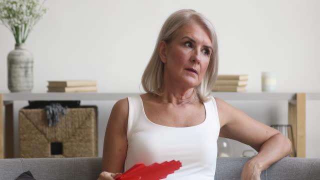vidéos et rushes de femme plus âgée stressée respirant agitant la chaleur de sensation de ventilateur à la maison - canicule