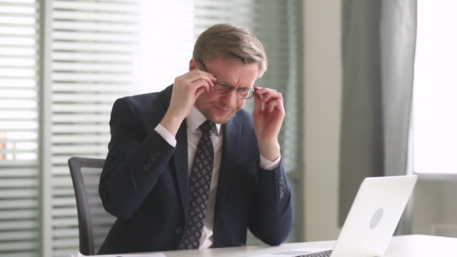 Stressed overworked businessman taking off glasses tired from computer