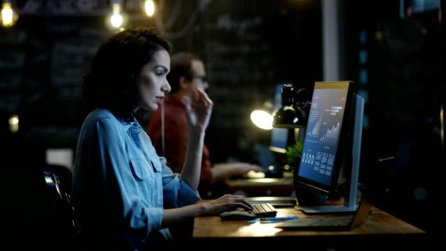 stockvideo's en b-roll-footage met ««««benadrukt, overwerkt vrouwelijke financier houdt haar hoofd in handen terwijl u werkt op een personal computer. in de achtergrond creatieve office. - overwerken
