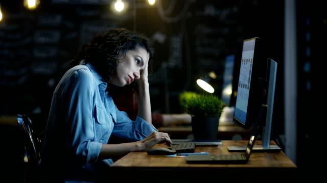vidéos et rushes de souligné, surchargés de travail téléphone mobile app concepteur détient sa tête féminine en mains tout en travaillant sur un ordinateur personnel. dans le bureau créatif de fond. - stress