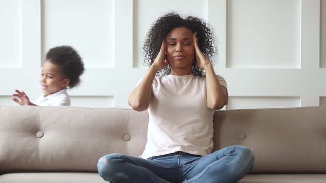 stressed upset african mom feeling headache tired of active kids - genitori video stock e b–roll