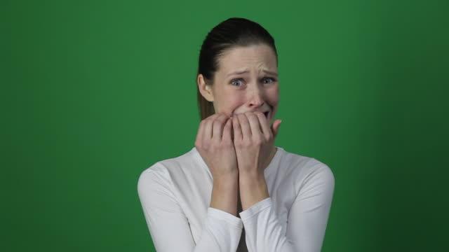 stressad kvinna rädd, gnaga naglar och titta på kameran. - fruktan bildbanksvideor och videomaterial från bakom kulisserna