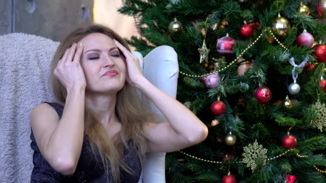 Stressed woman with headache on christmas tree background. Indoor sad young woman video