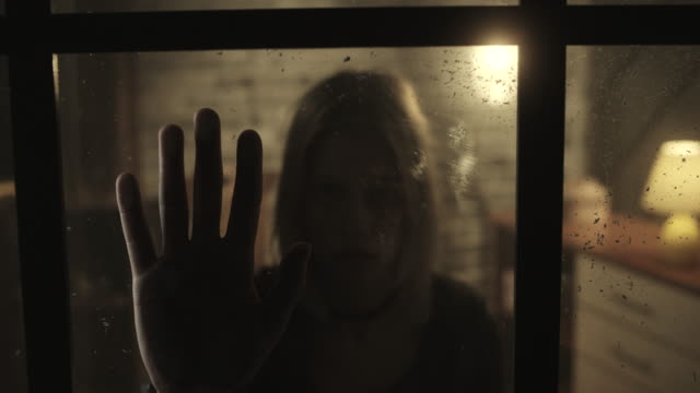 stressed women holding hand inside of the window - violenza sulle donne video stock e b–roll