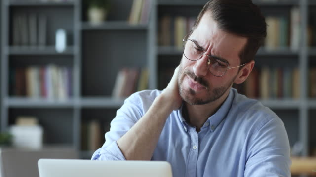 Stressed young man in glasses suffering from muscles tension.